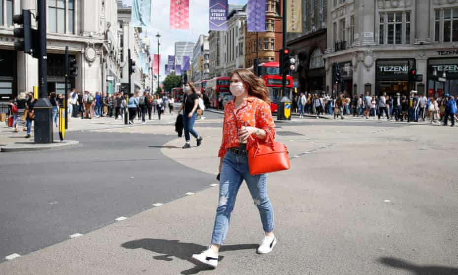 A shopper wearing a face covering crosses the street at Oxford Circus