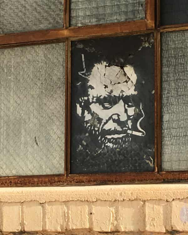 A stencil of poet Charles Bukowski, by Elvis Segarich, adorns a window in San Pedro.