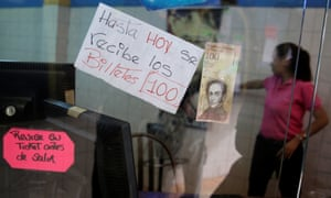 A 100 bolivar note is seen next to a sign that reads '100 bolivar notes are received until today,' at a store in Caracas, Venezuela on Monday.