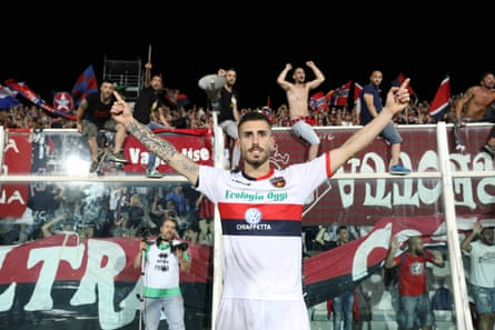 Fans celebrate behind Gennaro Tutino, one of the scorers in Cosenza's play-off victory.