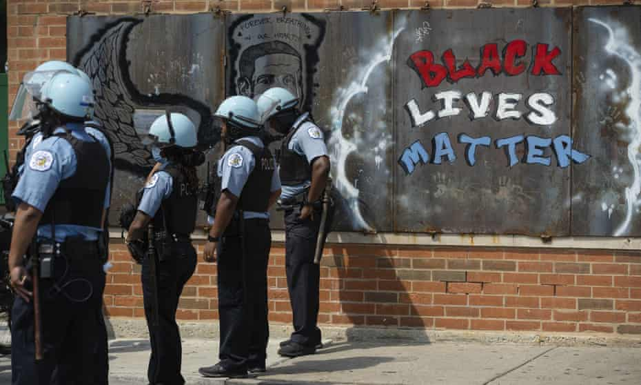 Police officers stand beside a mural for George Floyd in the neighborhood of Bronzeville, in Chicago, during an anti-police brutality protest.