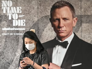 A woman wearing a facemask walks past a poster for the new James Bond movie No Time to Die in Bangkok, Thailand.