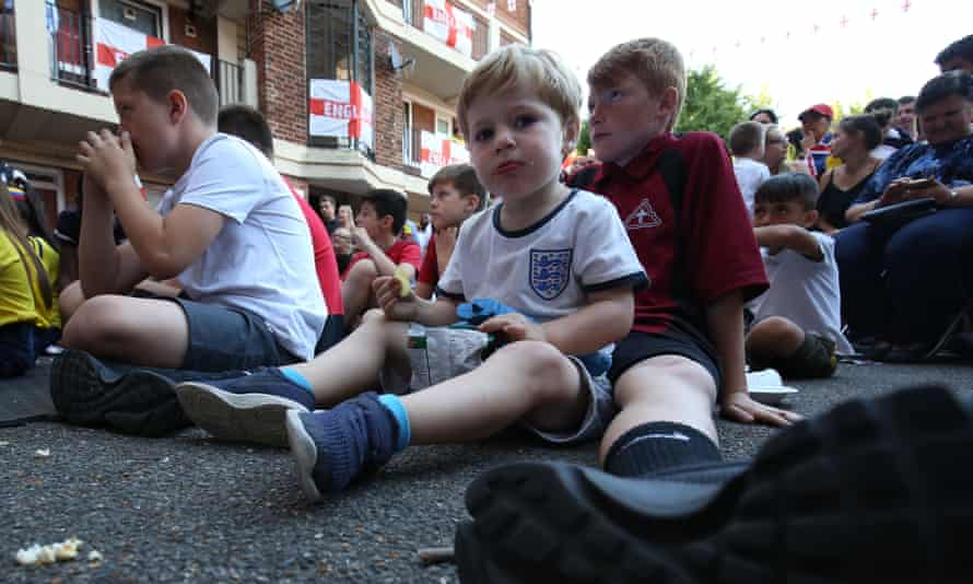 A young England fan in London eats crisps as he watches the Colombia-England game.