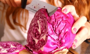 Young woman cutting red cabbage