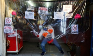 A man cleans a plastic sheet installed as a protective measure at local shop in Mexico City, Mexico 3 May 2020.