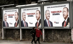 People walk past AKP billboards with pictures of Erdoĝan and mayoral candidate Binali Yıldırım in Istanbul.