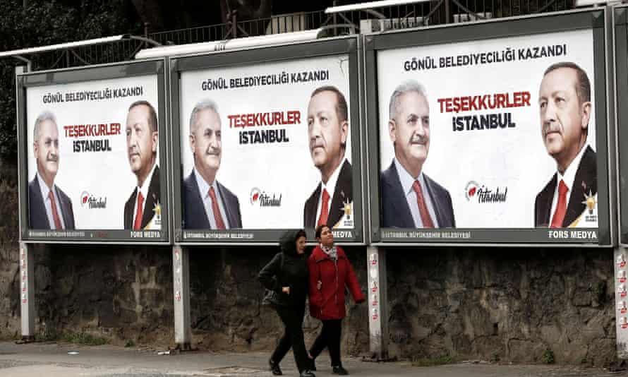 People walk past AKP billboards with pictures of Erdoĝan and mayoral candidate Binali Yıldırım in Istanbul.
