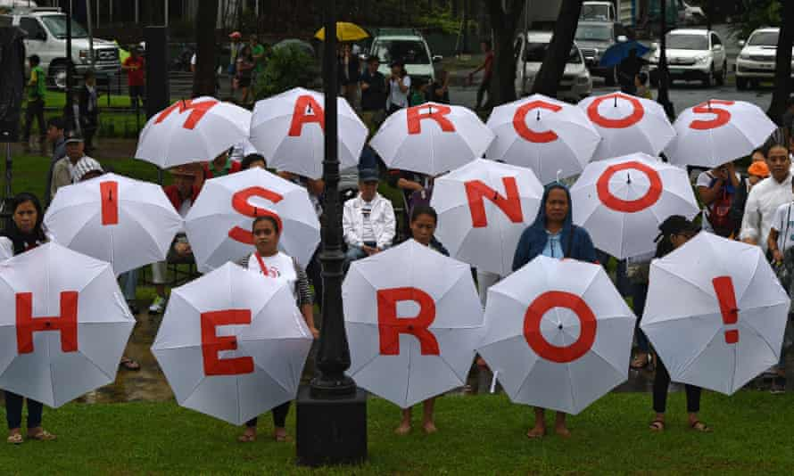 People hold umbrellas with an anti-Marcos message, in Rizal Park.