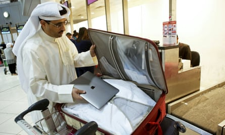 A man puts his laptop inside his suitcase at Kuwait international airport.