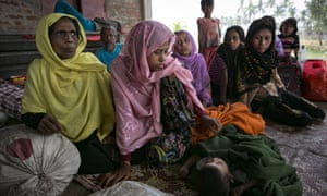Rohingya women and children rest after crossing into Bangladesh at Cox's Bazar on Friday, a day after the two governments signed a refugee repatriation deal.