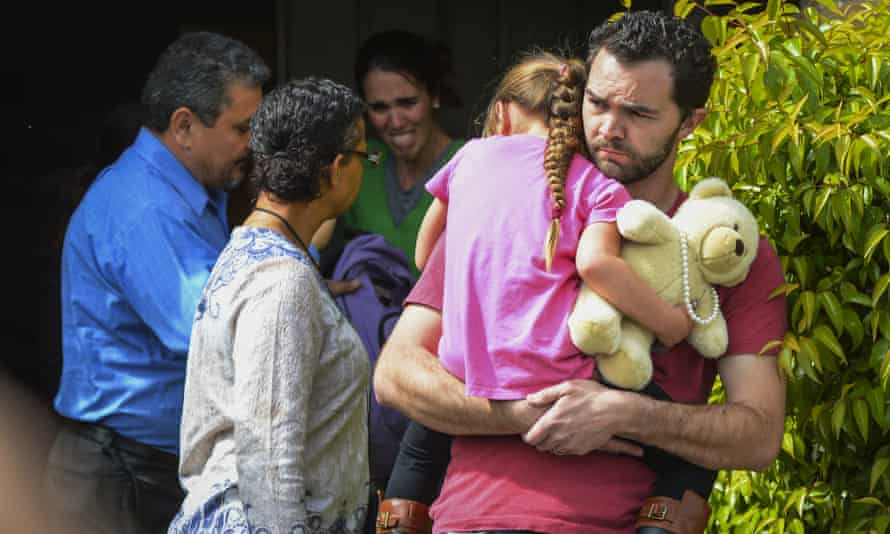 Foster father Rusty Page carries Lexi while Summer Page, in the background, cries as members of family services arrive.
