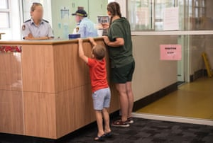 A child and mother approach the prison guards' desk.