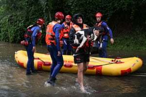 A NSW SES rescue team brings a local resident and his dog to safety