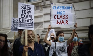 People including students hold placards on Whitehall outside Downing Street in London as they protest against the downgrading of A-level results.