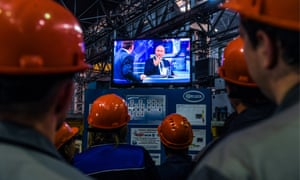 Workers watch a live broadcast of the question and answer session