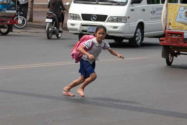 A young girl crosses a busy road in Cambodia