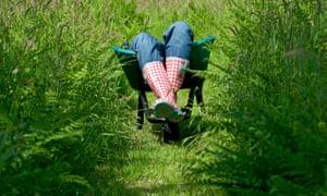 female laying in garden wheelbarrow