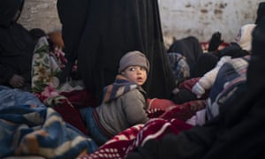 Women and children sit in the back of a truck as they wait to be screened by the SDF on the outskirts of Baghuz