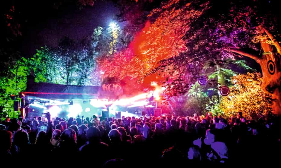 Night time shot of revellers at Kelburn Garden Party, North Ayrshire. The trees around the stage are lit up in an assortment of colours.