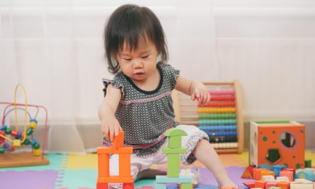 Baby girl playing with toy blocks at home