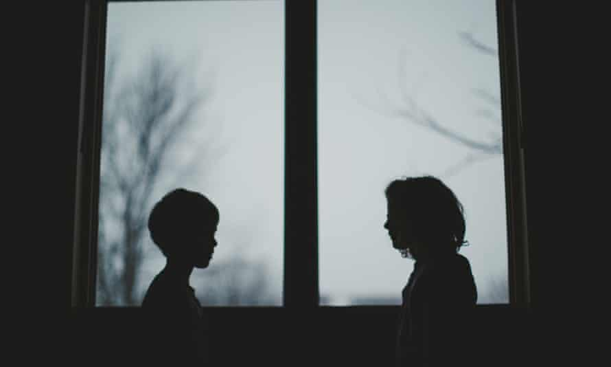 Boy and girl in silhouette by window