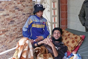 A wounded Isis fighter is eager to shake our hands. A boy wearing an IS hat and an AC Milan sweatshirt stands beside him.