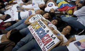 Opposition supporters lie on the ground during a demonstration outside the Organization of American States office building in Caracas, Venezuela, on Thursday.