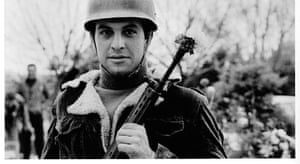 An Iranian revolutionary with a flower in his rifle.