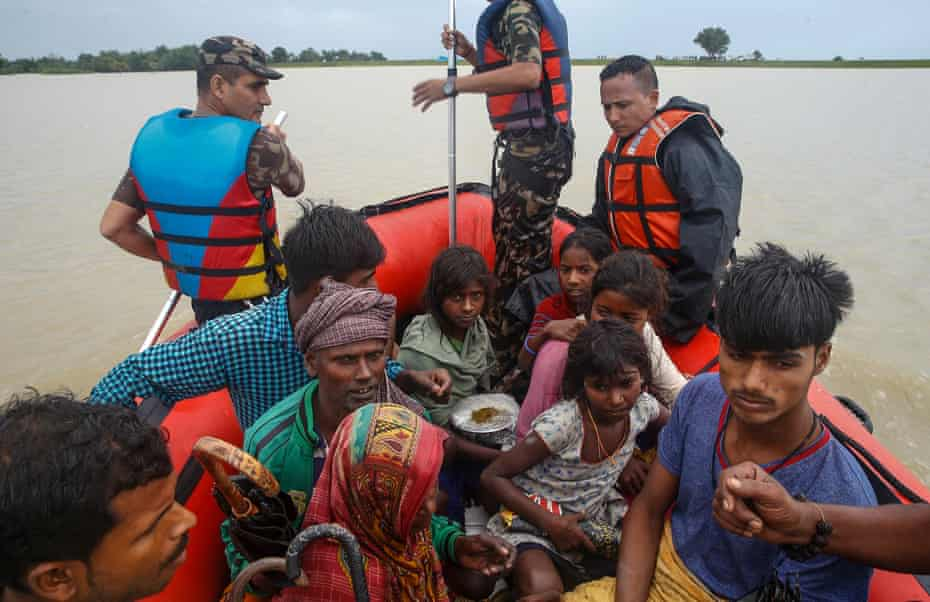 Flood victims are taken to safety by Nepalese soldiers from their flood-hit village of Kulari, Saptari.