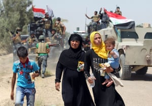Iraqi families walk along the road past pro-government forces after fleeing the city