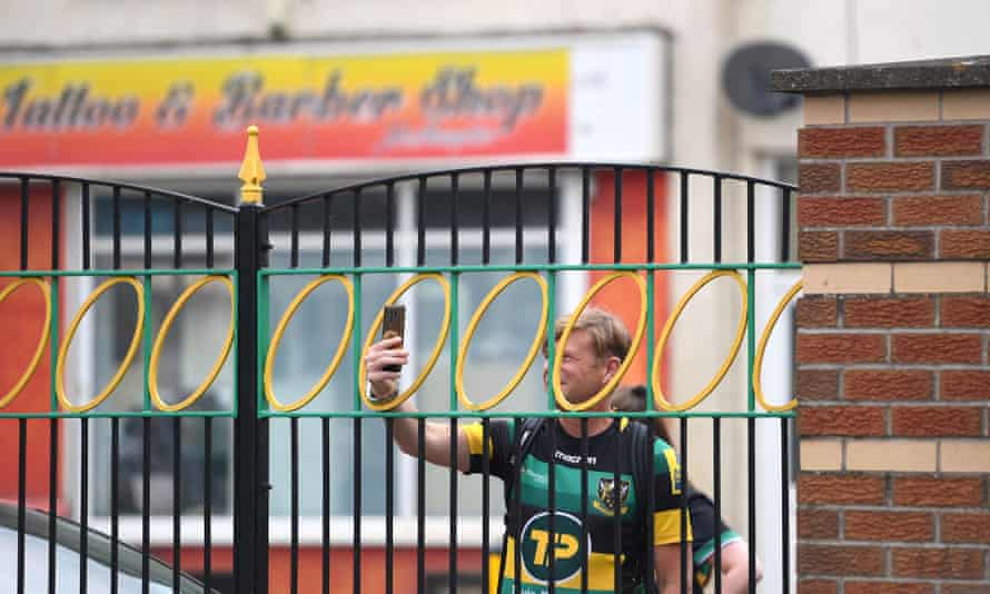 A Northampton fan takes a picture through the locked gates before a Premiership match against Wasps at Franklin's Gardens.