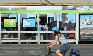 Morning commuters board a tram at a platform as a cyclist rides past in Melbourne, Australia
