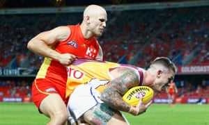 Dayne Beams is tackled by Gary Ablett during the match between the Gold Coast Suns and the Brisbane Lions at Metricon Stadium on Saturday.