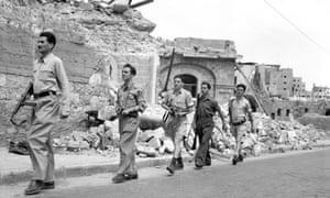 Members of the Haganah patrol the ruins of Haifa in May 1948
