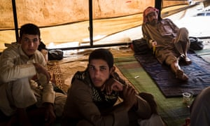 Civilians who fled the fighting in Deir al Zour rest inside a tent at the Ain Issa IDP camp.