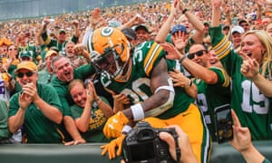 Green Bay fans celebrate with running back Jamaal Williams during a game last season