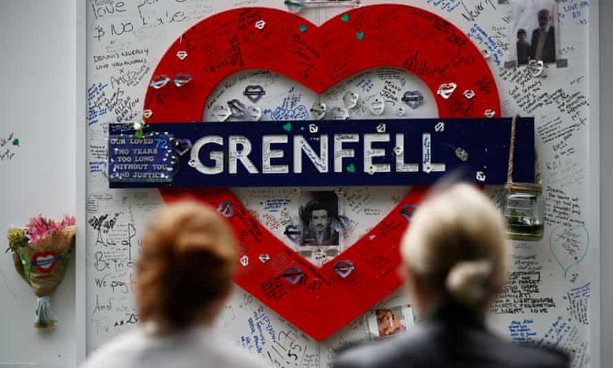 Two women look at messages of condolence at the base of Grenfell Tower