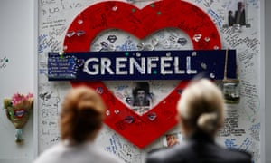 Women look at a hoarding covered in messages of condolence at the base of Grenfell tower.