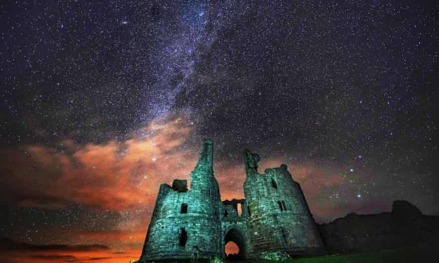 Starry skies above Dunstanburgh Castle ruins in Northumberland.
