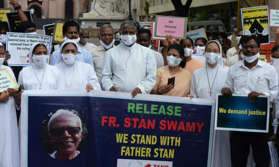 Catholic priests and nuns hold a sign saying 'Release Fr Stan Swamy –we stand with Father Stan'