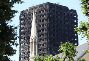 A church spire stands in the foreground of Grenfell Tower.