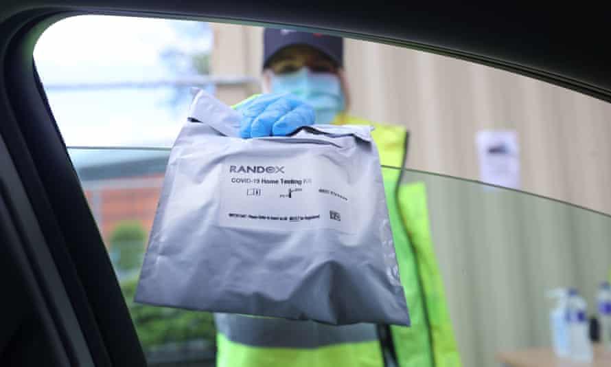 A member of staff hands over a Randox self-test kit
