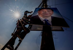 A government worker installing a poster of Xi Jinping on a pylon