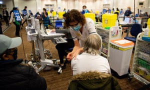 Members of the public receive a dose of a Covid-19 vaccine at a temporary vaccination centre at Villa Park football stadium in Birmingham.