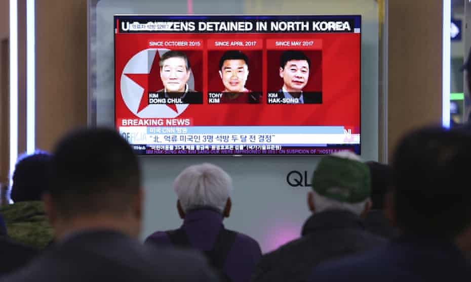 People watch a TV news report screen showing portraits of three Americans, Kim Dong Chul, Tony Kim (Kim Sang-duk) and Kim Hak Song, detained in the North Korea, at the Seoul railway station in South Korea.