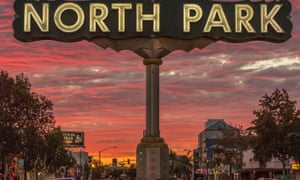 The sign to North Park in the foreground with the neighbourhood behind beneath a dramatic sunset