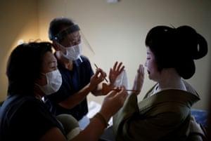 Mitsunaga Kanda, a makeup artist and Yurie Hatanaka, a wig stylist, wear protective face masks and face shields as they work on Tokijyo Hanasaki, a jiutamai dancer