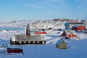 Churches and small red buildings on snow by waterfront in Ilulissat