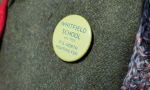 A badge saying: 'Whitfield School, Est. 1757. It's worth fighting for.'