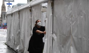 A waitress wears a face mask as she is closing up the outside tent of the Grill in Aberdeen